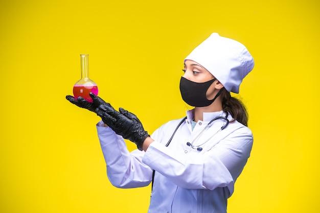 Młoda pielęgniarka w masce na twarz i dłoń trzyma chemiczną kolbę powyżej i sprawdza ją.