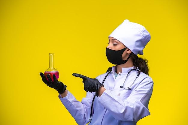 Młoda pielęgniarka w masce na twarz i dłoń trzyma kolbę chemiczną i wskazuje na nią palcem.