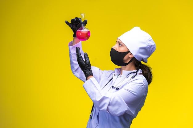 Młoda pielęgniarka w masce na twarz i dłonie śledzi reakcję w butelce i zostaje zaskoczona.