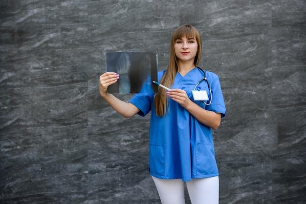 Młoda pielęgniarka w mundurze wskazuje na problemy zdrowotne. rtg stopy. pojęcie medyczne.