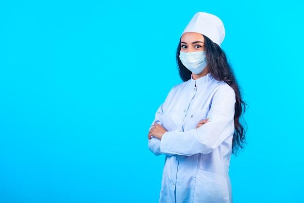 Młoda pielęgniarka w odosobnionym mundurze, trzymając się za ręce i dając pewność siebie