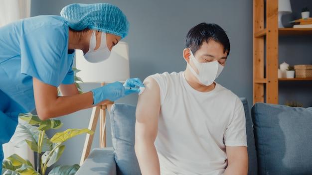 Młoda pielęgniarka z azji podaje szczepionkę przeciw wirusowi covid-19 lub grypie pacjentowi płci męskiej noszącej maskę ochronną przed chorobą wirusową