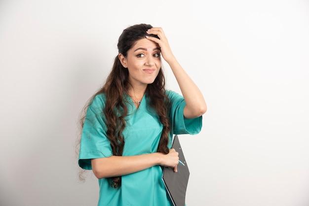 Młoda pielęgniarka z schowkiem i ołówkiem.