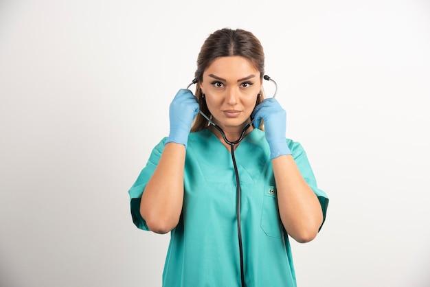 Młoda pielęgniarka zakłada stetoskop.