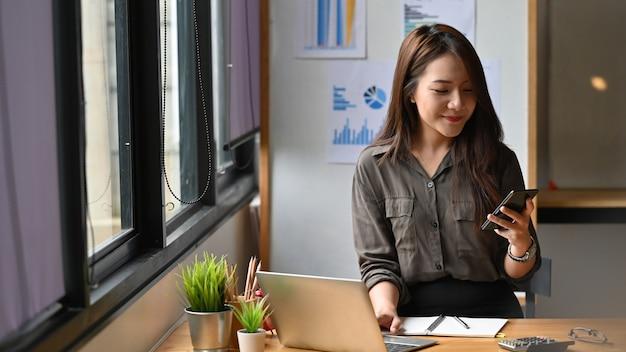 Młoda pieniężna kobieta kalkuluje dane na smartphone.