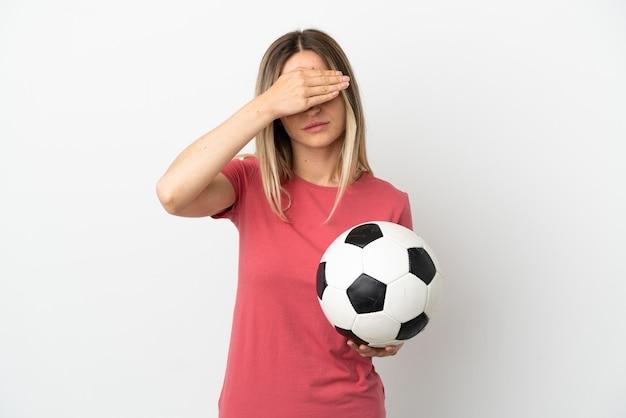 Młoda piłka nożna gracz kobieta na pojedyncze białe ściany obejmujące oczy przez ręce. nie chcę czegoś widzieć