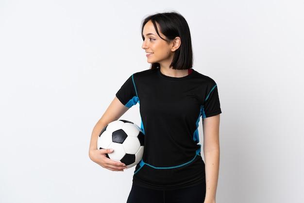 Młoda piłka nożna kobieta na białym tle patrząc z boku