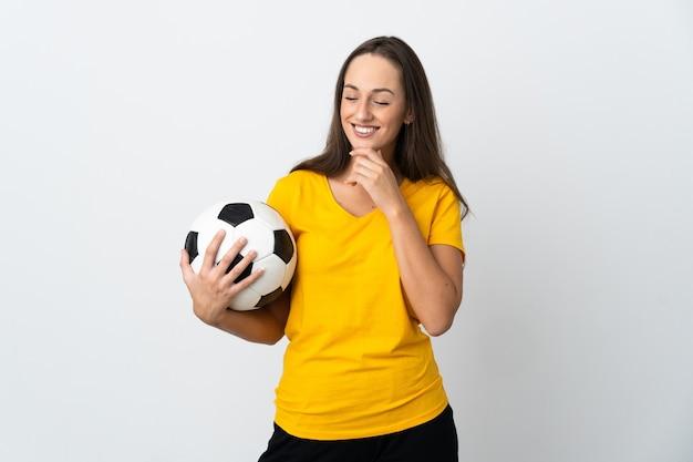 Młoda piłkarka kobieta na białym tle, patrząc w bok i uśmiechając się