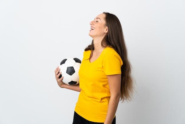 Młoda piłkarka kobieta na białym tle śmiejąca się w pozycji bocznej