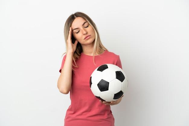 Młoda piłkarka kobieta na odosobnionej białej ścianie z bólem głowy