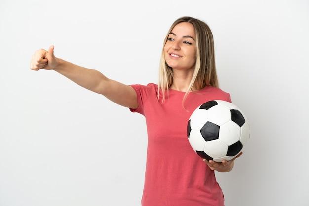 Młoda piłkarka kobieta nad odosobnioną białą ścianą, dając gest kciuka w górę