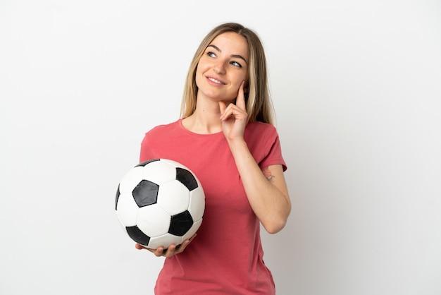 Młoda piłkarka kobieta nad odosobnioną białą ścianą, myśląc o pomyśle, patrząc w górę