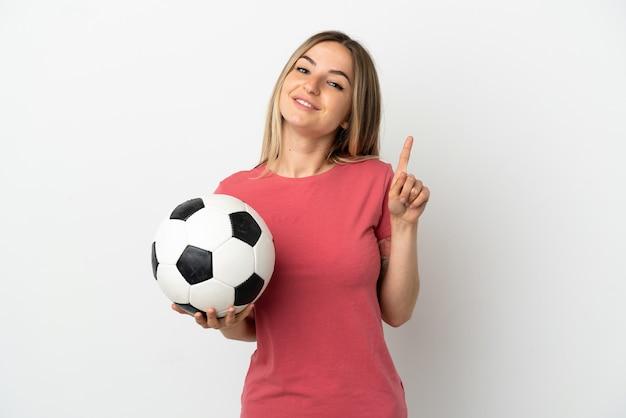 Młoda piłkarka kobieta nad odosobnioną białą ścianą pokazującą i unoszącą palec na znak najlepszych