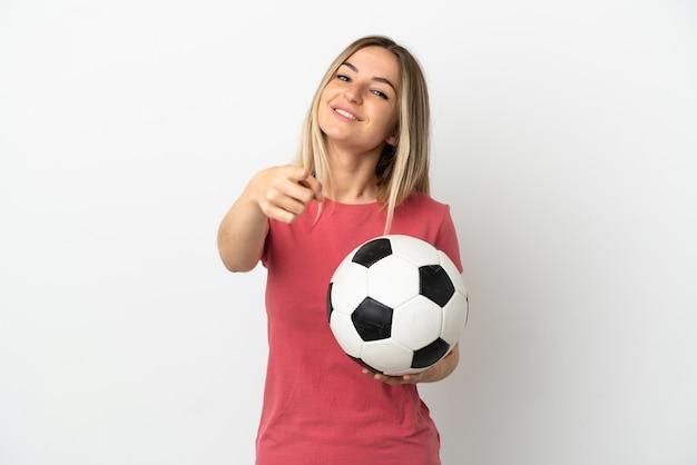 Młoda piłkarka kobieta nad odosobnioną białą ścianą wskazującą przód z szczęśliwym wyrazem twarzy