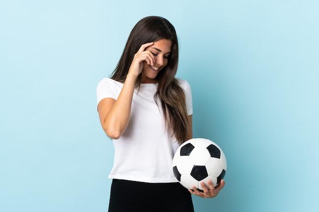 Młoda piłkarz brazylijska dziewczyna odizolowana na niebieskim tle śmiejąc się