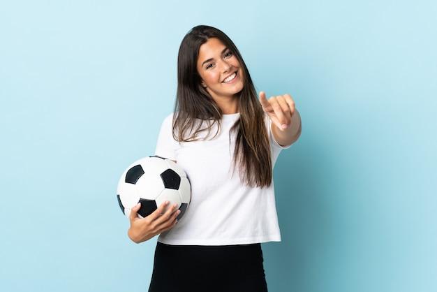 Młoda piłkarz brazylijska dziewczyna odizolowana na niebieskim tle wskazująca przód ze szczęśliwym wyrazem