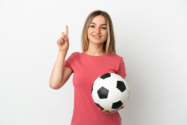 Młoda piłkarz kobieta nad odosobnioną białą ścianą wskazującą świetny pomysł