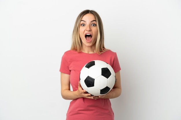 Młoda piłkarz kobieta nad odosobnioną białą ścianą z niespodzianką wyrazem twarzy facial