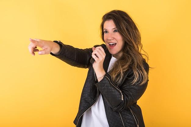 Młoda piosenkarka dziewczyna, ubrana w czarną skórzaną kurtkę, śpiewa z mikrofonem i wskazuje ręką na żółto.