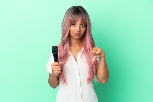 Młoda piosenkarka rasy mieszanej z różowymi włosami na białym tle na zielonym tle pokazując kciuk w dół z negatywną ekspresją