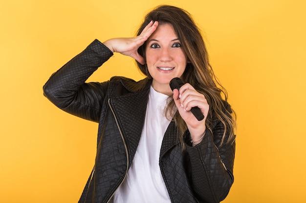 Młoda piosenkarka, ubrana w czarną skórzaną kurtkę i mikrofon, z prawą ręką na głowie, na żółto.