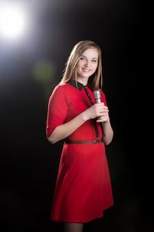 Młoda piosenkarka żeńska w czerwonej sukni