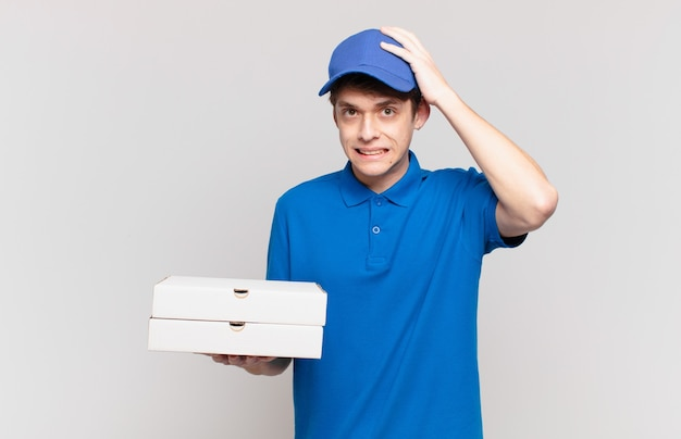 Młoda pizza dostarcza chłopca zestresowany, zmartwiony, niespokojny lub przestraszony, z rękami na głowie, panikujący z powodu błędu