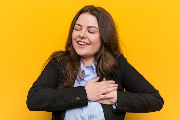 Młoda plus rozmiar kaukaski kobieta biznesu śmiejąc się trzymając ręce na sercu, szczęścia.
