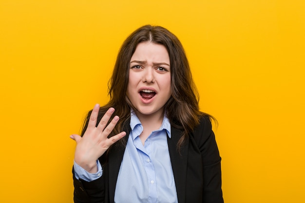 Młoda plus rozmiar kaukaski kobieta krzyczy z wściekłości.