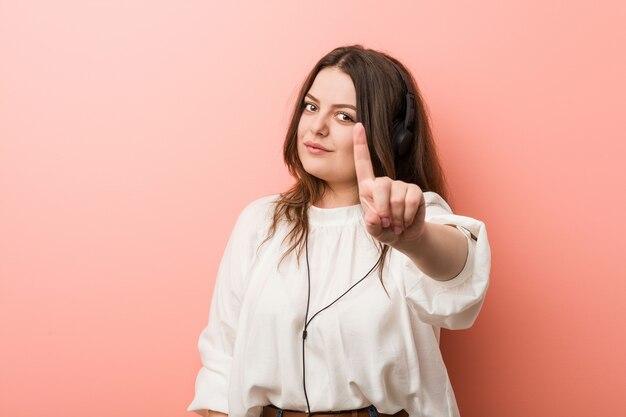 Młoda plus rozmiar krzywego kobieta słuchanie muzyki w słuchawkach pokazuje numer jeden z palcem.