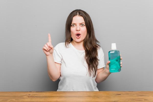 Młoda plus rozmiar krzywego kobieta trzyma płyn do płukania jamy ustnej o jakiś świetny pomysł, koncepcja kreatywności.