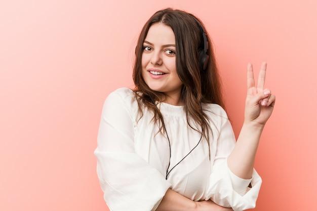 Młoda plus rozmiar krzywego kobiety słuchania muzyki ze słuchawkami pokazując numer dwa palcami.