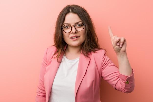 Młoda plus size biznesowa caucasian kobieta pokazuje liczbę jeden z palcem.