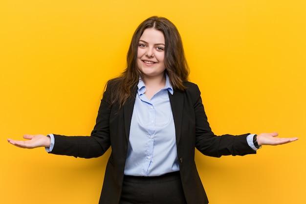 Młoda plus size caucasian biznesowa kobieta pokazuje mile widziany wyrażenie.