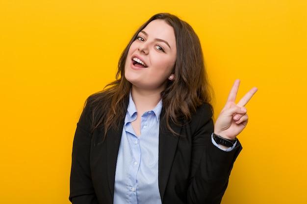 Młoda plus size kaukaska biznesowa kobieta radosna i beztroska pokazuje symbol pokoju z palcami.