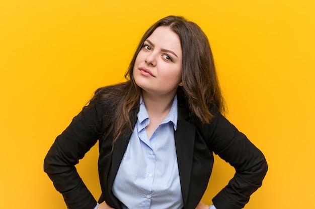 Młoda plus size kaukaska biznesowa kobieta zbeształ kogoś bardzo gniewnego.