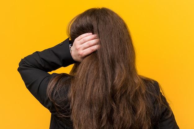 Młoda plus size kaukaska kobieta biznesu od tyłu myśli o czymś.