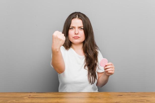 Młoda plus size kobieta o krągłych twarzach z gąbką do twarzy z pięścią do agresywnego wyrazu twarzy.