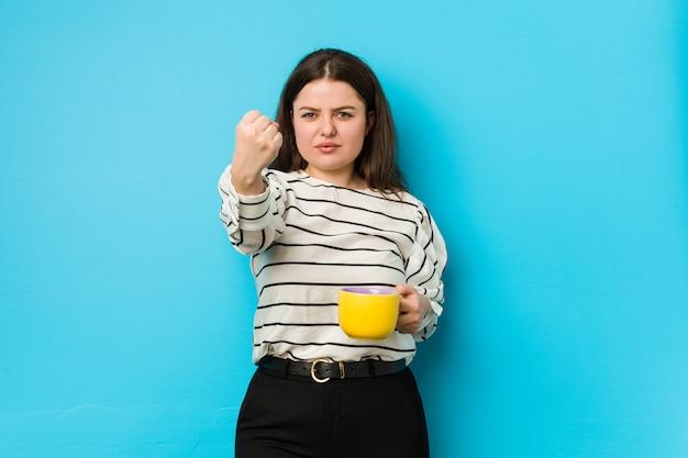 Młoda plus size kobieta trzyma kubek herbaty pokazując pięść do aparatu, agresywny wyraz twarzy.