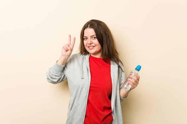 Młoda plus size krągła kobieta trzyma butelkę wody pokazując znak zwycięstwa i uśmiechając się szeroko.