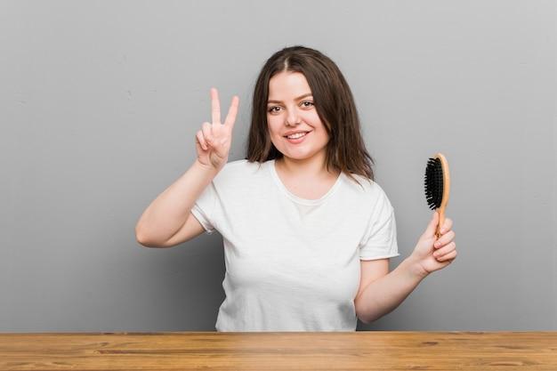 Młoda plus size krągła kobieta trzymająca szczotkę do włosów pokazująca znak zwycięstwa i uśmiechnięta szeroko.