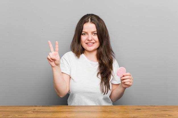 Młoda plus size kręcona kobieta trzyma twarzową gąbkę pokazującą numer dwa palcami.