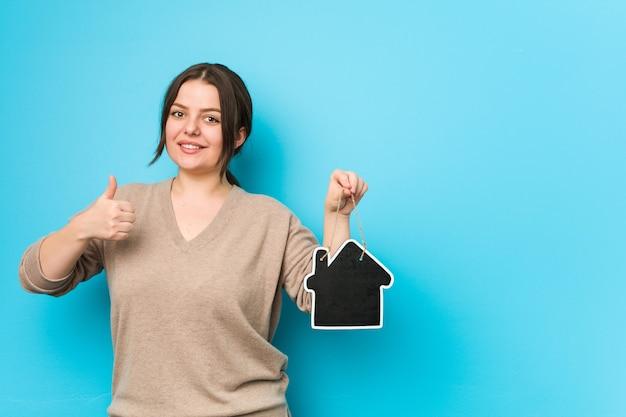 Młoda plus size kręty kobieta trzyma ikonę domu, uśmiechając się i podnosząc kciuk
