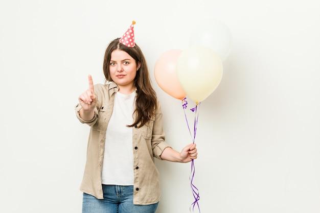 Młoda plus size krzywego kobieta świętuje urodziny z numerem jeden palcem.