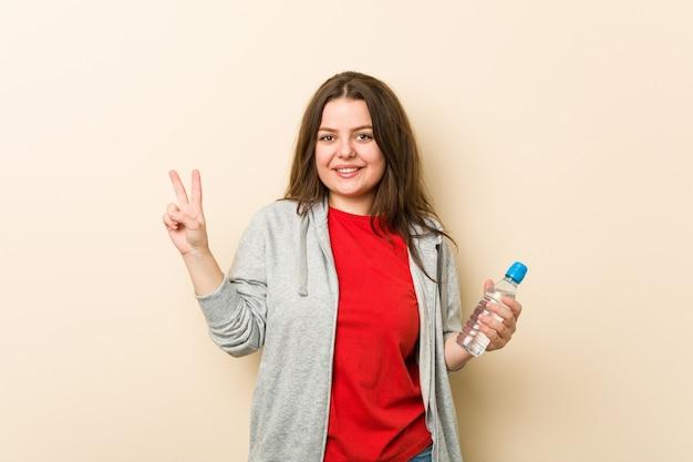 Młoda plus size krzywego kobieta trzyma butelkę wody pokazano numer dwa palcami.