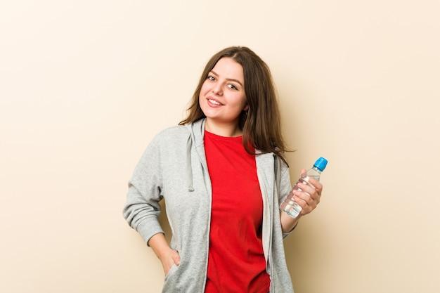 Młoda plus size krzywego kobieta trzyma butelkę wody szczęśliwa, uśmiechnięta i wesoła.