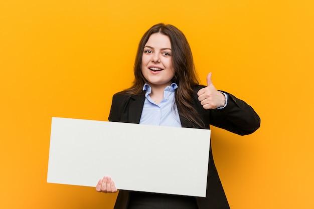Młoda plus size krzywego kobieta trzyma plakat uśmiechając się i podnosząc kciuk do góry