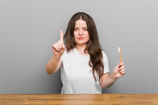 Młoda plus size krzywego kobieta trzyma szczoteczkę do zębów pokazano numer jeden palcem.