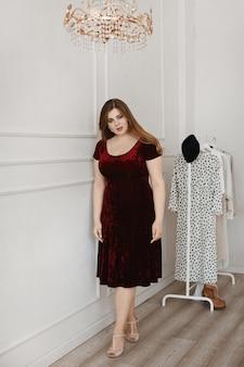 Młoda plus size model dziewczyna w czerwonej aksamitnej sukni pozuje w studiu.