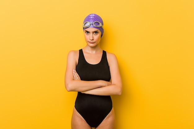 Młoda pływaczka kaukaski kobieta marszcząc brwi z niezadowoleniem, trzyma założone ręce.